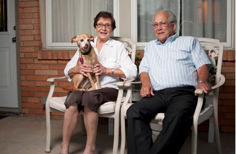 A senior couple sitting on the porch of their own home with their dog