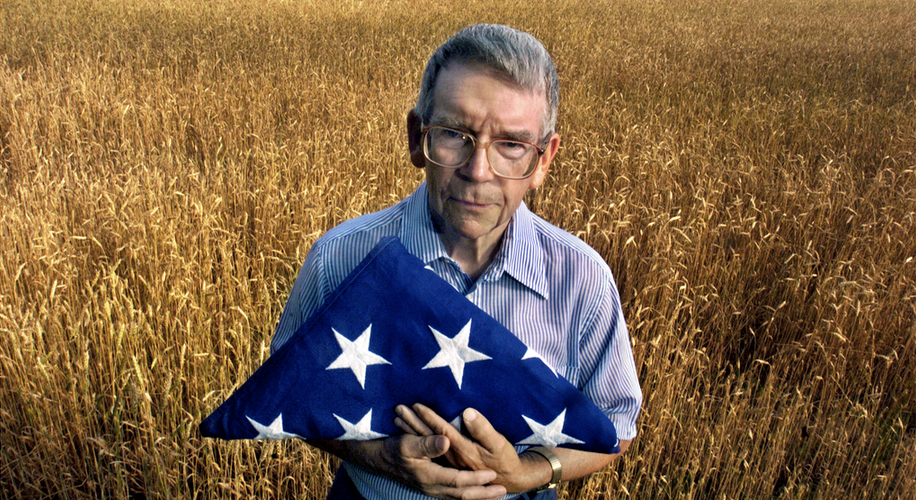 Senior veteran stands in a field holding a folded American flag - Idaho and Wyoming Veteran Senior Home Care
